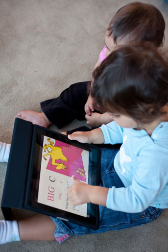 Toddlers playing with an iPad app