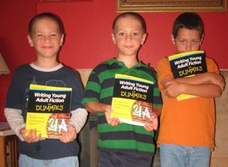 Deborah Halverson's triplet sons, displaying her latest book