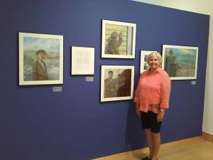 Helen Foster James (co-author with Virginia Loh Hagan) next to oil paintings and sketches from their book